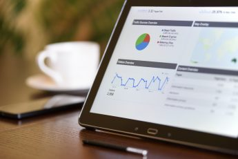 Ecommerce SEO charts and analytical data on the tablet screen with a cup of coffee and a telephone in the background